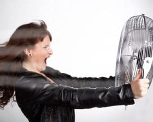 woman suffering from hot flashes holding fan in front of face
